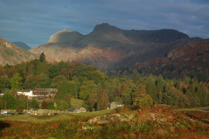 Autumn sunshine and dark skies over the Langdale Pikes.