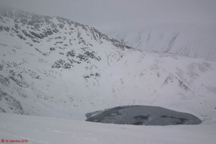 A gloomy looking Scales Tarn, with the bottom part of Sharp Edge behind.