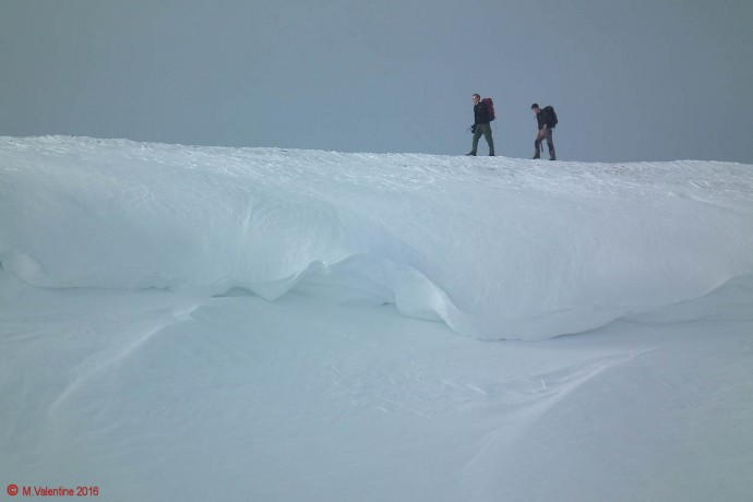"Two walkers above a large cornice on the ""Saddleback"" ridge."